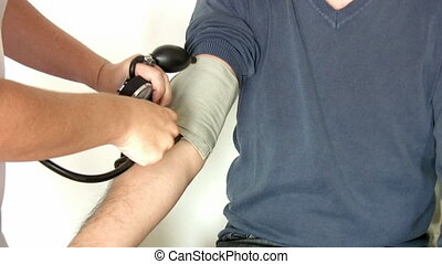 Checking blood pressure - Female doctor checking blood...