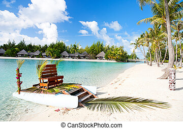 Polynesian wedding boat with chair at exotic beach