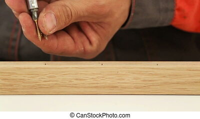 Screw - Carpenter driving screw into wooden desk selective...