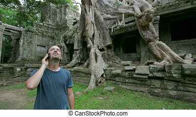 Young man talking phone in angkor