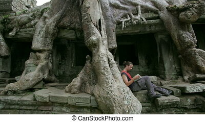 Young man reading book in angkor