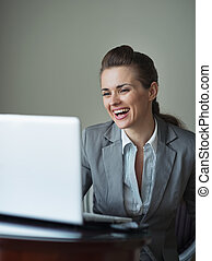 Smiling business woman in hotel room looking in laptop