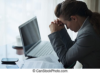 Stressed business woman working sitting at desk in hotel...
