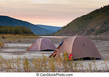 Tents at Yukon River in remote taiga wilderness