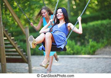 young women swinging