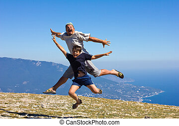 happy man and boy jumping over the Crimean Mountains and the Black Sea