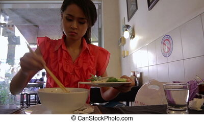 Asian girl eating noodle