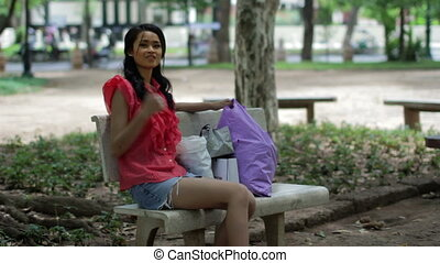 Asian girl resting bank bench