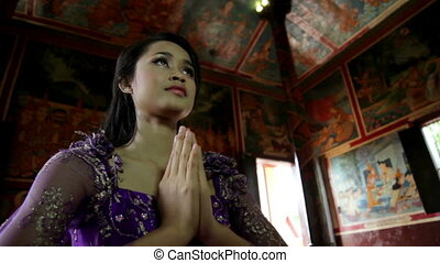 Asian girl praying in temple