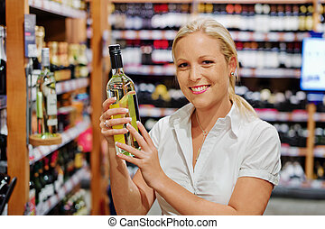 woman in a supermarket wine shelf - a woman buys wine in a...
