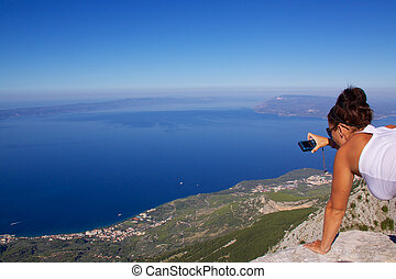 Makarska Riviera - Young girl photographing panoramic view...