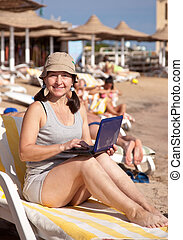 mature woman  with laptop at resort beach