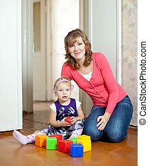 mother plays with baby  in home