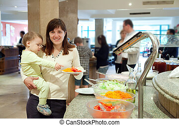 Woman with chid chooses   vegetables  in buffet