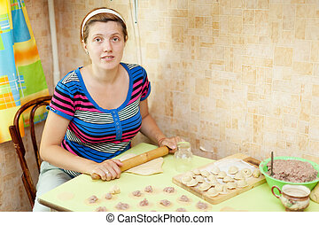 Woman making dumplings (pelmeni) in her kitchen