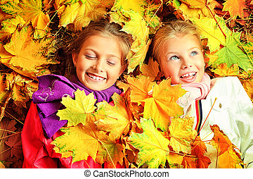 maple leaf fall - Portrait of two cute girls sisters posing...