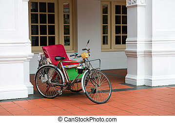 Empty bicycle rickshaw near classical colonial building,...