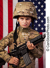 Boy USA soldier in front of American flag with rifle. Young...