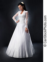 Fashionable young female brunette in white bridal dress...