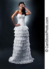 Lovely bride brunette in white dress standing in studio...