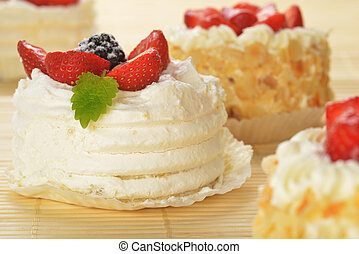 Small cakes with white icing and fruits on bamboo table...