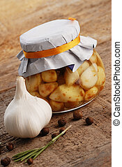 jar of pickled garlic with rosemary and pepper