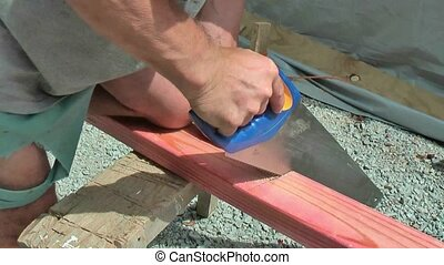 Carpenter using handsaw. - New Zealand. Carpenter cutting...
