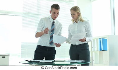 Teamwork and paperwork - Business team of two working with...