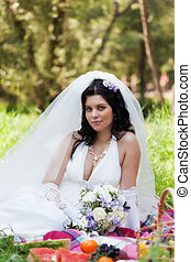beautiful bride sits on a grass with a big basket with fruit
