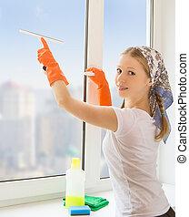 young housewife washing the window - beautiful young...