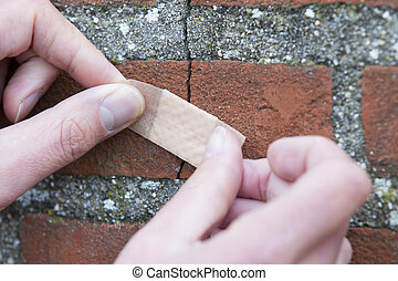 Man Applying Duct Tape On Cracked Wall - Mans hands applying...