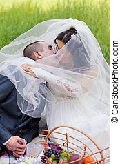 groom and the bride together sit on a grass with a big...