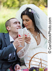 groom and the bride together sit on a grass with champagne...