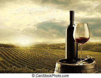 Vineyard at sunset - red wine bottle and wine glass on...