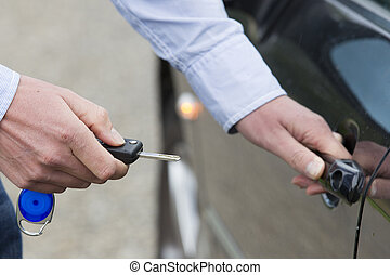 Man Unlocking Car Door. - Cropped view of man with key...