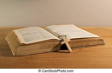 old bible book with wooden cross on table