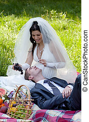 happy bride treats the groom with grapes