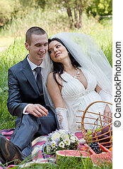 groom and the bride sit on a grass with a big basket with...