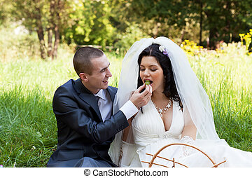 happy groom treats the bride with ripe grapes