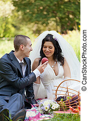 groom treats the bride with a ripe peach