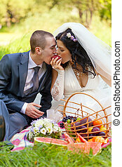 groom and the bride together eat a ripe peach