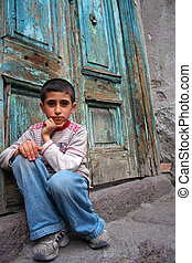 boy sitting at the doorstep