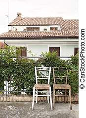 Two vintage chairs on a sidewalk in a southern Europe, Italy, perfect place for relaxation & retire
