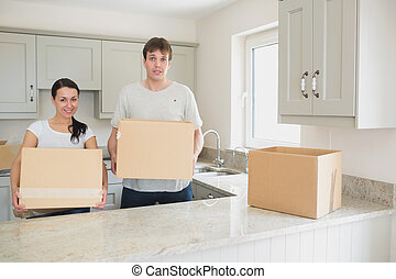 Young couple relocating - Young couple standing in the...