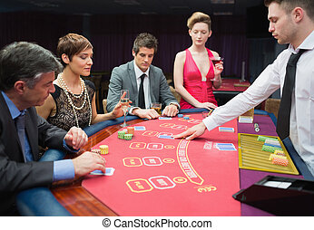 Four people playing poker in casino
