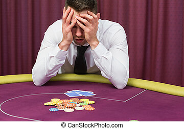 Man holding head in hands at poker table in casino