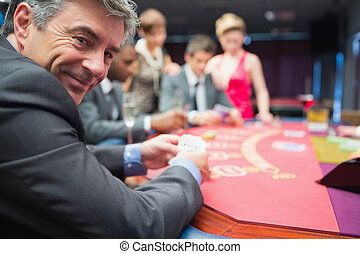Man smiling at the poker table in casino