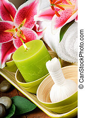 Spa setting with candle and herbal ball