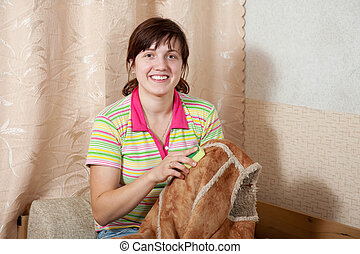 Woman cleaning shammy vest with sponge at home