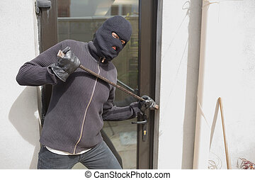 Robber breaking into house using crow bar - Robber breaking...
